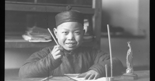 Smiling_boy_seating_at_a_table_writing,_China,_ca._1918-1938_(MFB-LS0248A)